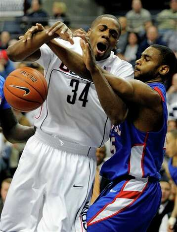 UConn;sAlex Oriakhi, left, fights for a rebound with DePaul's Eric Wallace during the first half of their men's NCAA college basketball game in Storrs, Conn., on Saturday, Feb. 6, 2010  Photo: AP Photo/Fred Beckham