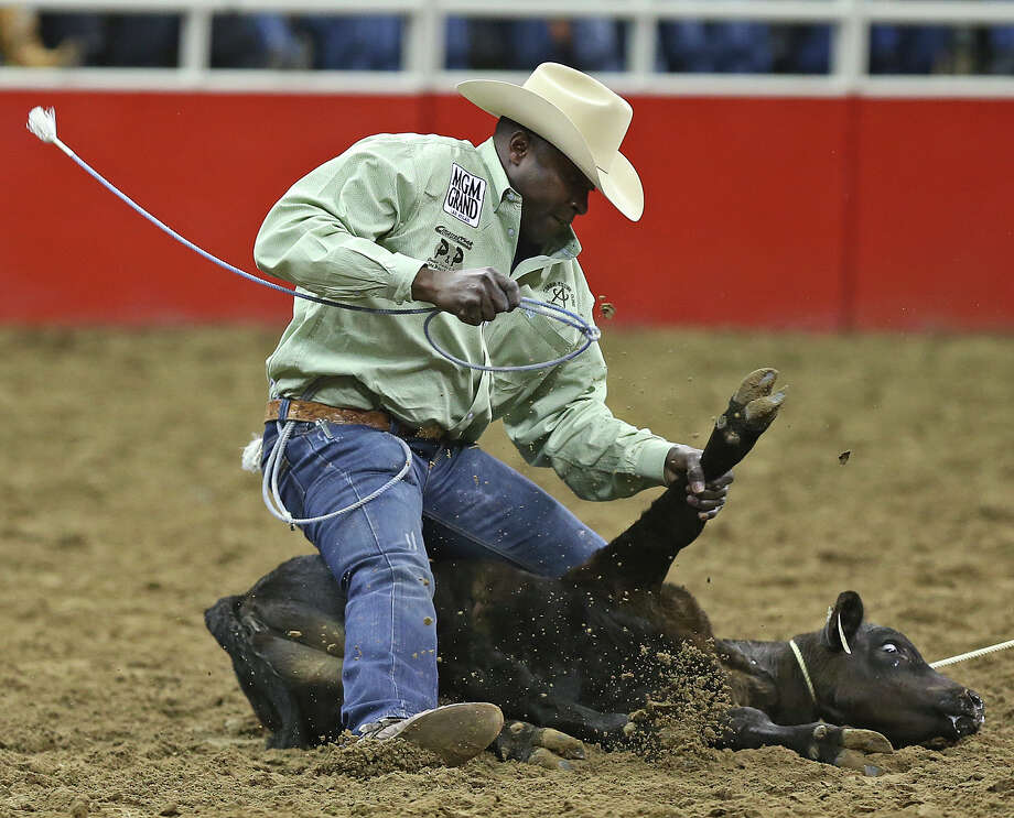 Fred Whitfield, of Hockley, Texas, is the first contestant in the Tie-Down Roping competition at the San Antonio Stock Show Rodeo at the AT&T Center, Wednesday, Feb. 12, 2014. Whitfield logged a time of 10.5 seconds. Photo: Jerry Lara, San Antonio Express-News / ©2013 San Antonio Express-News