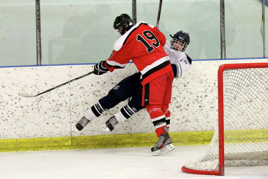 Fairfield's #19 Kevin Boldrighini checks Staples/Weston/Shelton's #18 Evan Mancini into the boards during Wednesday evening match up at Milford Ice Pavilion. Photo: Mike Ross / Mike Ross Connecticut Post freelance -www.mikerossphoto.com