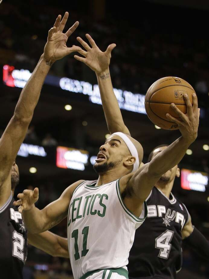 Boston Celtics guard Jerryd Bayless (11) drives to the basket against San Antonio Spurs forward Kawhi Leonard (2) and guard Danny Green (4) during the second half of an NBA basketball game in Boston, Wednesday, Feb. 12, 2014. The Spurs defeated the Celtics 104-92. (AP Photo/Stephan Savoia) Photo: Associated Press