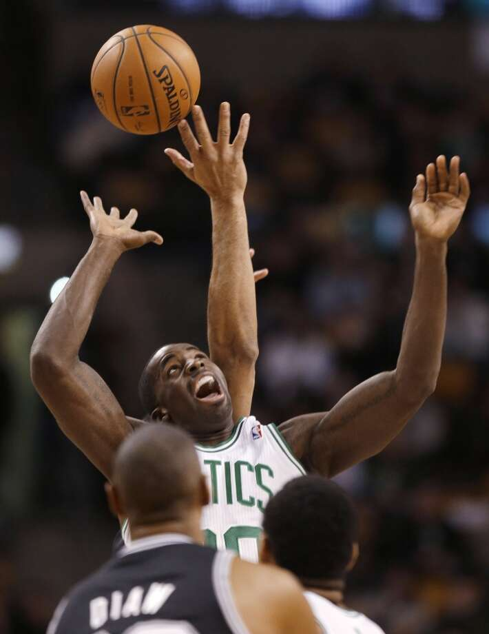 Boston Celtics power forward Brandon Bass (30) strains to reach the ball as San Antonio Spurs forward Tim Duncan controls the opening top of an NBA basketball game in Boston, Wednesday, Feb. 12, 2014. (AP Photo/Stephan Savoia) Photo: Associated Press