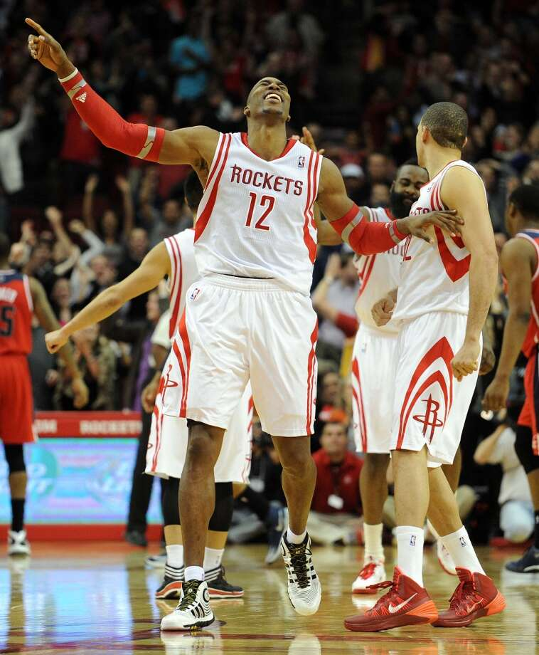 Houston Rockets center Dwight Howard (12) celebrates teammate James Harden's eventual game-winning two-pointer with teammate Francisco Garcia. Photo: Eric Christian Smith, For The Chronicle