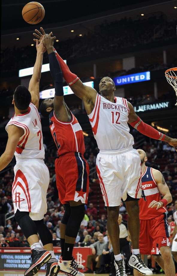 Houston center Dwight Howard, right, and guard Jeremy Lin, left, go up for a rebound with Washington guard John Wall. Photo: Eric Christian Smith, For The Chronicle