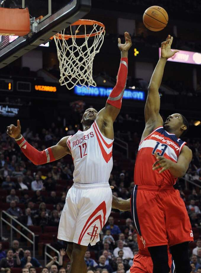 Houston center Dwight Howard, left, and Washington center Kevin Seraphin fight for a rebound. Photo: Eric Christian Smith, For The Chronicle