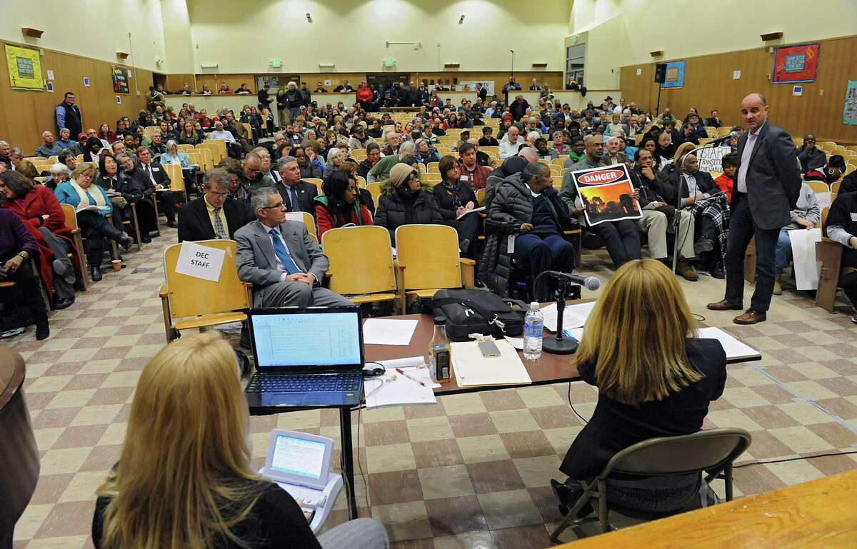 Chris Amato, of Environmental Advocates of New York, right, uses his two minutes at the microphone to speak his opinion at a public meeting about plans for crude oil facility at the nearby Port of Albany at Giffen Elementary School on Wednesday Feb. 12, 2014 in Albany, N.Y. (Lori Van Buren / Times Union)