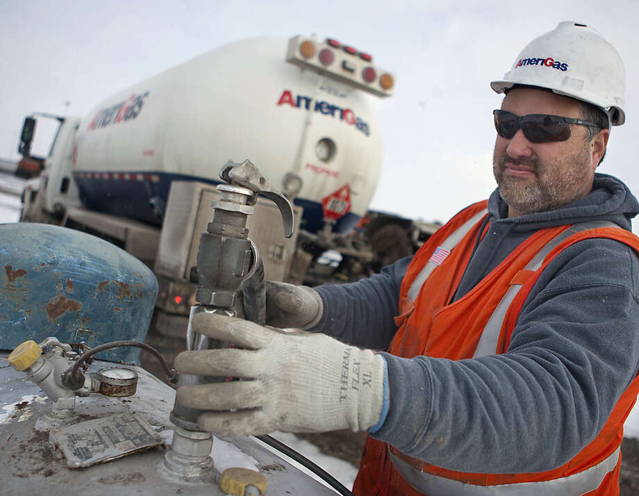 AmeriGas employee Jay Carlson prepares to remove a hose after filling a tank with propane near Galesburg, Ill., last month, when rough weather helped put a pinch on the state's supply. Photo: Associated Press File Photo / The Register-Mail