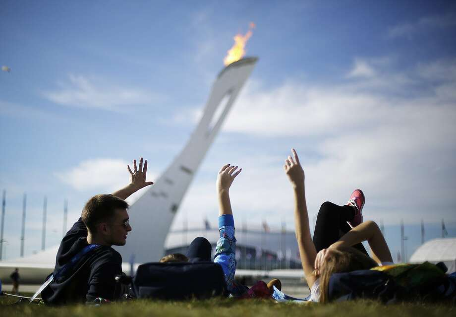 Volunteers from left, Vladimir Malakhov, Elena Ripenko, and Aleksandra Zhuk, lay out on the lawn under the Olympic cauldron at the 2014 Winter Olympics, Wednesday, Feb. 12, 2014, in Sochi, Russia. Temperatures are predicted near 60 degrees Fahrenheit in Sochi on Wednesday. (AP Photo/David Goldman) Photo: David Goldman, Associated Press