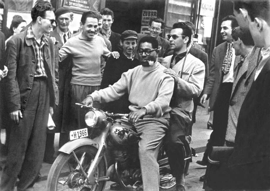 Dizzy Gillespie with Yugoslav musician and composer Nikica Kalogjera and fans. Zagreb, Yugoslavia, 1956  Courtesy of the Marshall Stearns Collection, Institute of Jazz Studies, Rutgers University Photo: Courtesy Of The Marshall Stearns