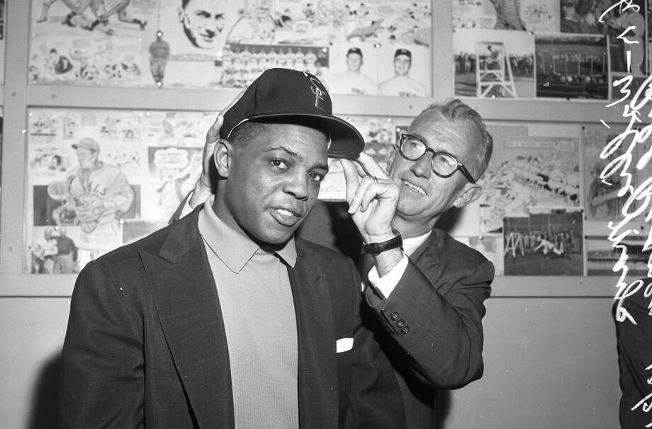 Oct. 31, 1957: Willie Mays gets his hat fitted by manager Bill Rigney, during the center fielder's first visit to Seals Stadium. Note the gallery of Seals players in the background. Photo: Joe Rosenthal, The Chronicle