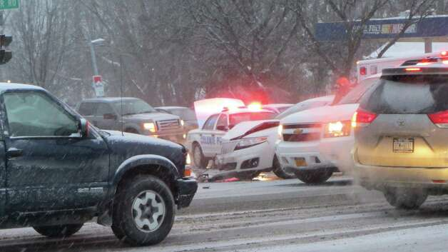 As the snow started to fall Thursday, police and firefighters responded to a car crash at the interesection of Albany Shaker Road and Wolf Road in Colonie. (Bob Gardinier / Times Union)