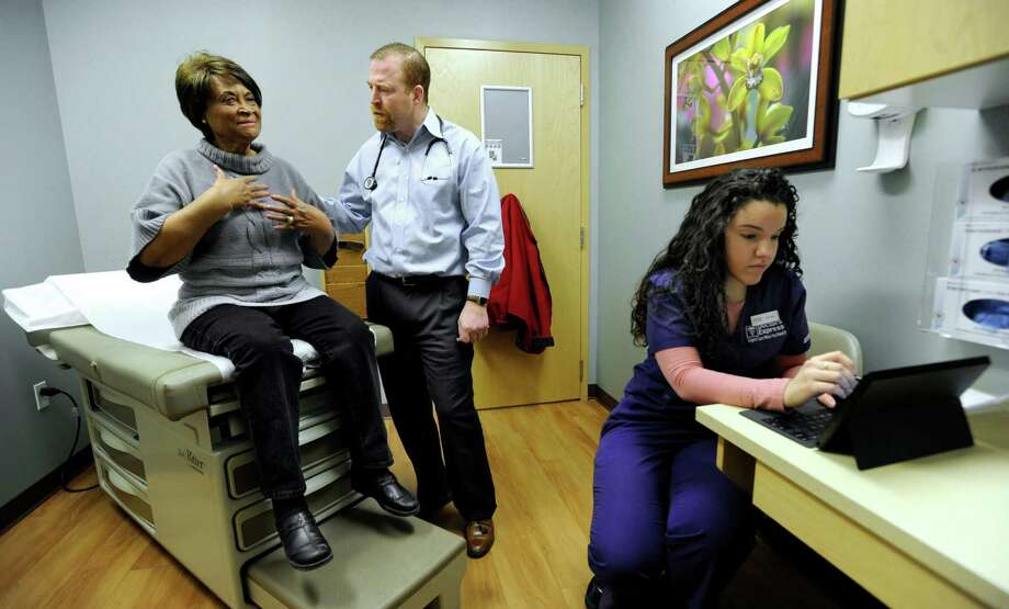 Esmie Lindsay, 72, of Danbury, Conn.  left, explains to Dr. Thomas Brown the symptoms that brought her to Doctors Express, an urgent care clinic on Main street in Danbury, Wednesday, Feb. 13, 2014. Right is medical assistent Daniela Milic, 24. Photo: Carol Kaliff / The News-Times