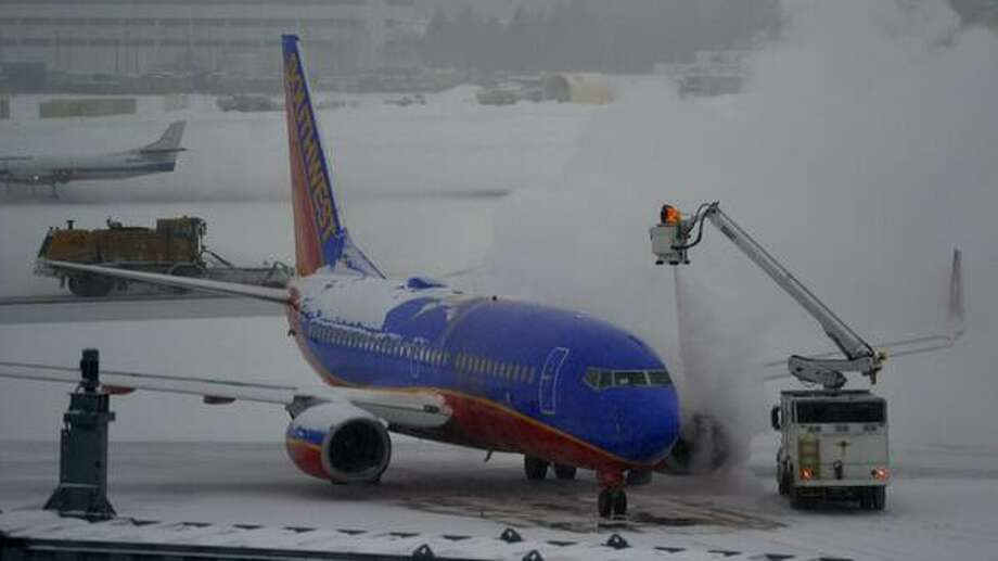 One of the last Southwest flights to leave Albany International Airport is deiced before heading to the runway Thursday morning. Southwest has canceled all flights out of Albany after 9:50 a.m. (Skip Dickstein / Times Union)