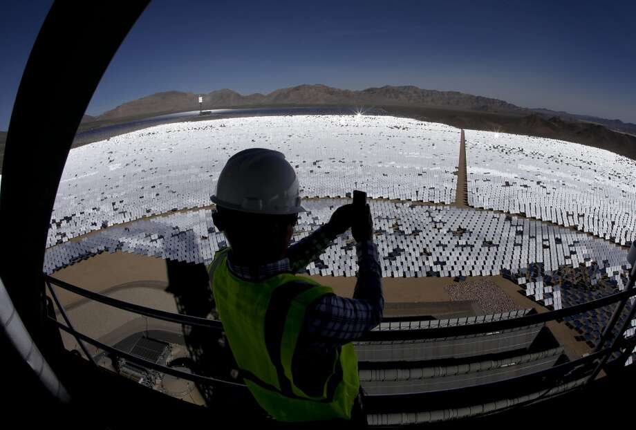 Jeff Holland takes a picture of some of the 300,000 computer-controlled mirrors that reflect sunlight to boilers that sit on 459-foot towers in Primm, Nev. The Ivanpah Solar Electric Generating System, sprawling across roughly 5 square miles of federal land near the California-Nevada border, will be opened formally Thursday after years of regulatory and legal tangles. Photo: Chris Carlson, ASSOCIATED PRESS