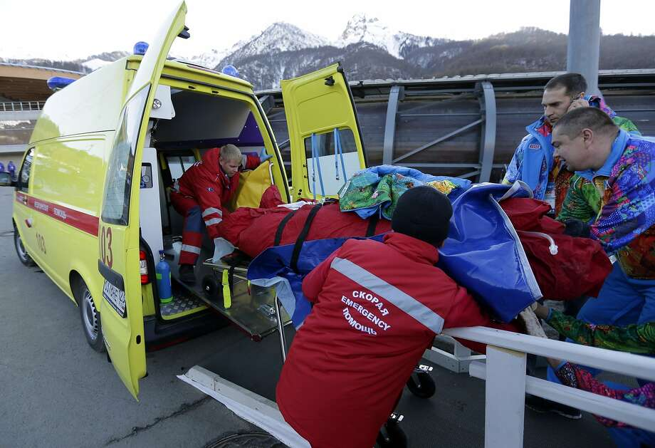 A track worker is loaded into an ambulance after he was injured when a forerunner bobsled hit him just before the start of the men's two-man bobsled training at the 2014 Winter Olympics, Thursday, Feb. 13, 2014, in Krasnaya Polyana, Russia.  Photo: Charlie Riedel, Associated Press