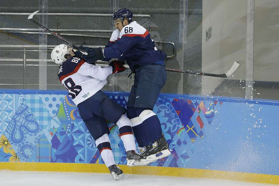 USA forward Patrick Kane and Slovakia defenseman Milan Jurcina battle up against the boards during the 2014 Winter Olympics men's ice hockey game at Shayba Arena, Thursday, Feb. 13, 2014, in Sochi, Russia. Photo: Matt Slocum, Associated Press