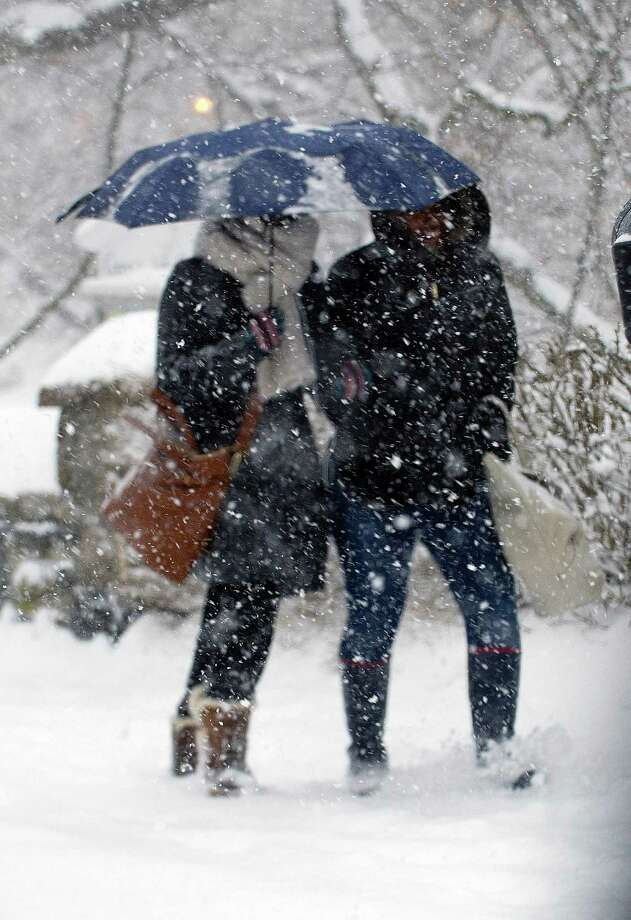 "Tyiesha Collins, left, and Ashley Richardson, right, share an umbrella as they walks through the snow in Greenwich, Conn., on Thursday, February 13, 2014. The two were walking to their jobs at Zara, where they said they would call the corporate office to see if they were to be open or closed. The snow made Richardson's commute extra difficult because she came into Greenwich from Bridgeport. ""For me it's a super super pain to get here and then they're like, 'Okay, you're closed, you can go home,'"" she said. Photo: Lindsay Perry / Stamford Advocate"