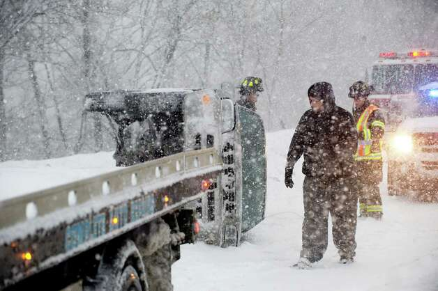 Emergency crews work on an overturned car on I-95 North between exits 3 and 4 in Greenwich, Conn., on Thursday, February 13, 2014. Photo: Lindsay Perry / Stamford Advocate