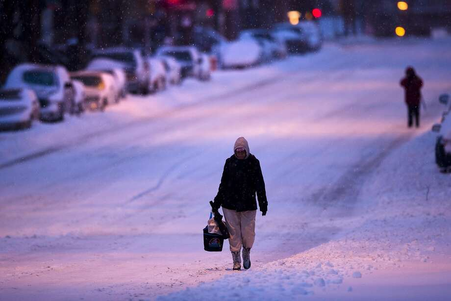 Morning commuters walks in the plowed road as mixed winter precipitation falls Thursday, Feb. 13, 2014, in Philadelphia. Snow and sleet are falling on the East Coast, from North Carolina to New England, a day after sleet, snow and ice bombarded the Southeast.  Photo: Matt Rourke, Associated Press