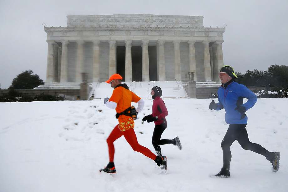 From  left, Alejandro Escobar, Courtney Fulton, and Trevor Albert, all from Arlington, Va., run in the snow past the Lincoln Memorial in Washington, Thursday, Feb. 13, 2014. After pummeling wide swaths of the South, a winter storm dumped nearly a foot of snow in Washington as it marched Northeast and threatened more power outages, traffic headaches and widespread closures for millions of residents.  Photo: Charles Dharapak, Associated Press