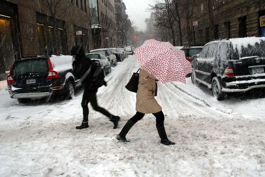 People walk through the snow on February 13, 2014 in New York City. In what is turning out to be one of the snowiest winter's in recent memory for New York City and much of the East Coast, Thursday's weather is expected to bring a wintery mix of sleet and snow with total accumulation of 6 to 8 inches of snow before ending early Friday morning.  Photo: Spencer Platt, Getty Images