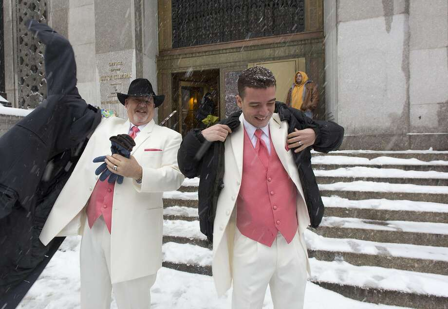 Newlyweds Steve Cosh, left, and Thiago Cardoso pull on their winter jackets as they step out from New York's municipal marriage bureau into a snow storm, Thursday, Feb. 13, 2014. Snow and sleet are falling on the East Coast from North Carolina to New England a day after sleet, snow and ice bombarded the Southeast. Photo: Mark Lennihan, Associated Press