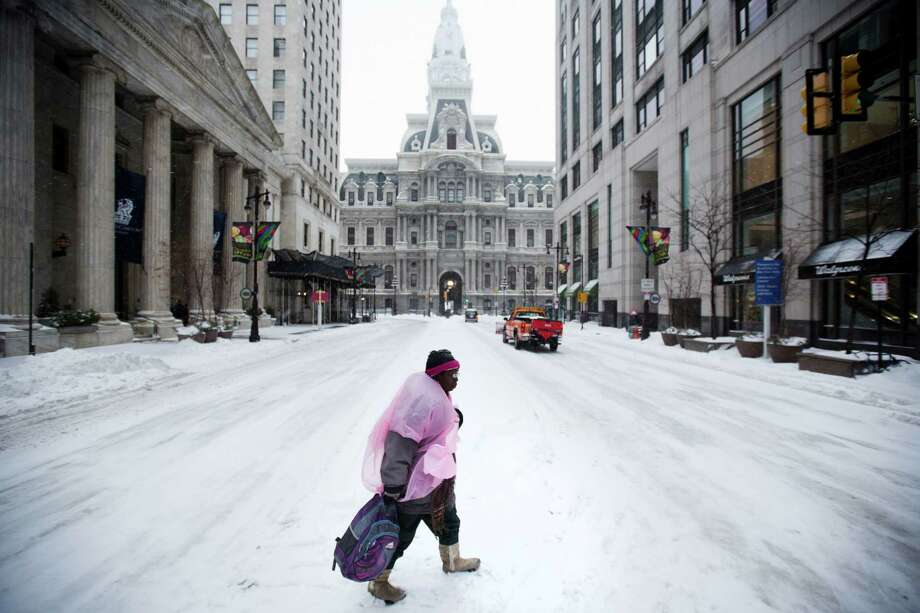 A pedestrian crosses South Broad Street in view of City Hall as mixed winter precipitation falls Thursday, Feb. 13, 2014, in Philadelphia. Snow and sleet are falling on the East Coast, from North Carolina to New England, a day after sleet, snow and ice bombarded the Southeast. Photo: Matt Rourke, AP / AP