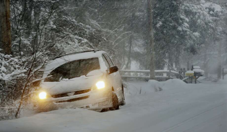A car sits stuck in the snow after skidding into a ditch in Yardley, Pa., Thursday, Feb. 13, 2014. After pummeling wide swaths of the Southeast, a winter storm dumped more than a foot of snow in parts of the Mid-Atlantic region as it marched Northeast and threatened more power outages, traffic headaches and widespread closures for millions of residents.  (AP Photo/Mel Evans) Photo: Mel Evans, Associated Press
