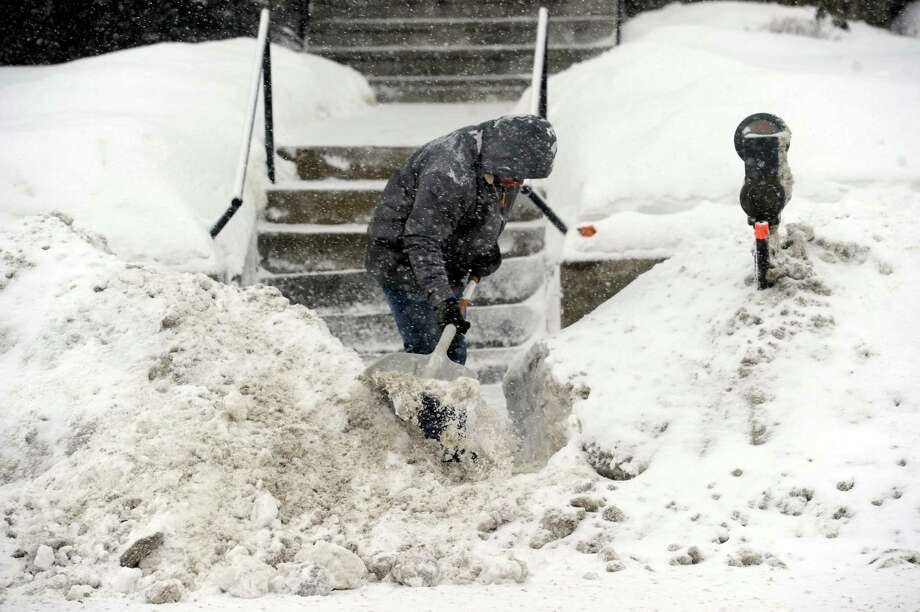 A man shovels fresh snow on West Street in Danbury, Conn., Thursday, Feb. 13, 2014, during the early stages of a snow storm. Photo: Carol Kaliff / The News-Times