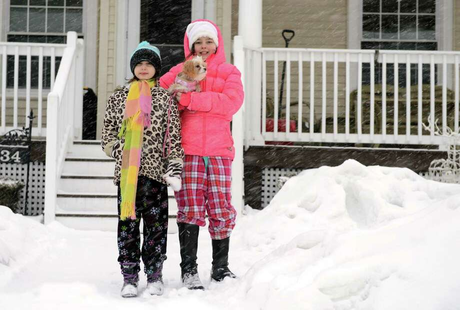 Sisters Samantha, 8, and Madison Palmieri, 10, take their dog Ginger out in the snow Thursday, Feb. 13, 2014, in Ansonia, Conn. Photo: Autumn Driscoll / Connecticut Post