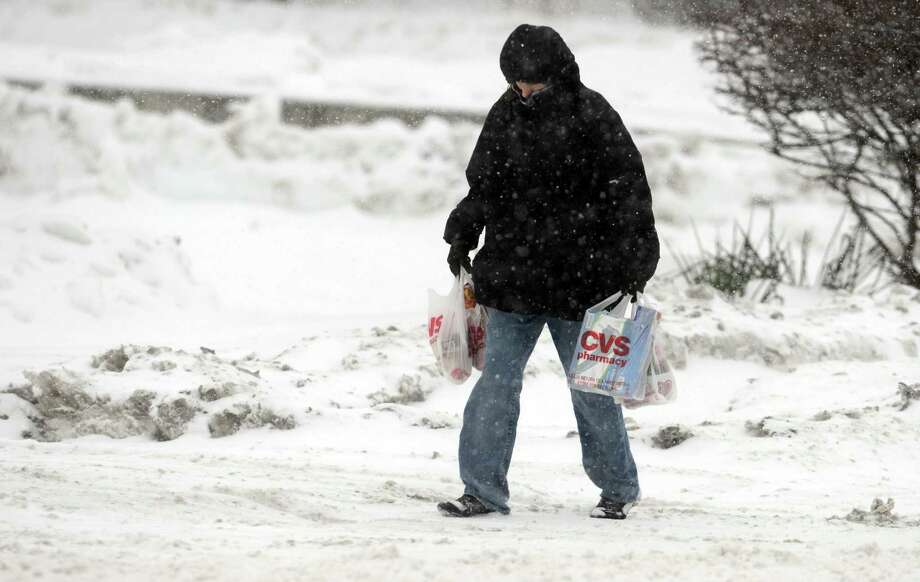 Laura Rogers, of Ansonia, walks home through the snow Thursday, Feb. 13, 2014, after shopping at CVS pharmacy in Ansonia, Conn. Photo: Autumn Driscoll / Connecticut Post