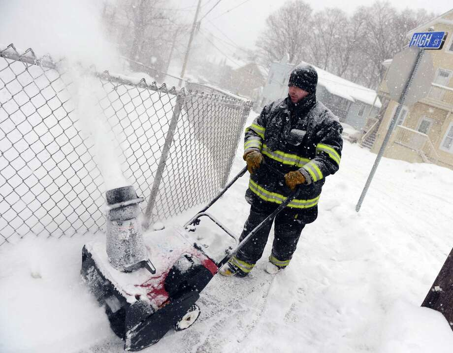 A firefighter clears snow around Fountain Hose Co. Thursday, Feb. 13, 2014, in Ansonia, Conn. Photo: Autumn Driscoll / Connecticut Post