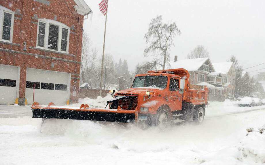 A plow removes snow from Howard Avenue Thursday, Feb. 13, 2014, in Ansonia, Conn. Photo: Autumn Driscoll / Connecticut Post