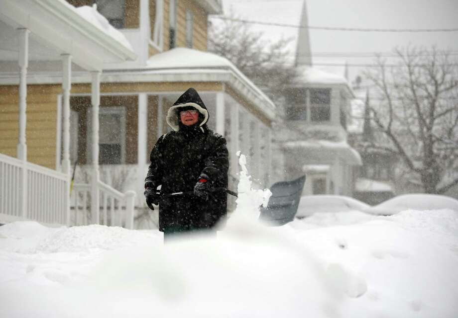 """Marge Roberts shovels her walkway Thursday, Feb. 13, 2014, in Ansonia, Conn. She wanted to get to work on shoveling before it starts sticking.  """"I'll be back out again later,"""" she said. Photo: Autumn Driscoll / Connecticut Post"""