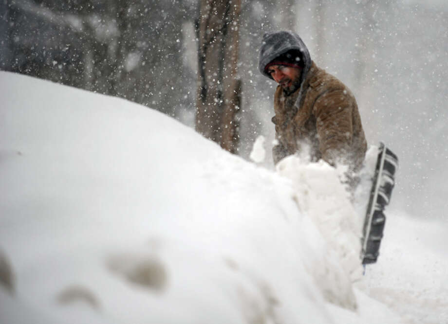A man shovels Thursday, Feb. 13, 2014, in Ansonia, Conn. Photo: Autumn Driscoll / Connecticut Post