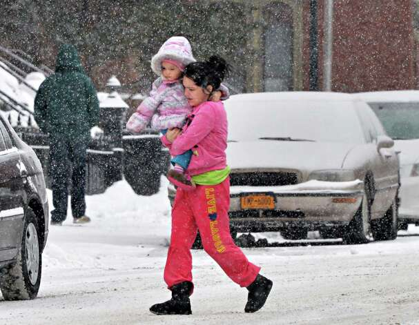 Brittany Cook of Cohoes rushes across Mohawk Street carrying her 2-year-old daughter Kendyl Cook as snow falls Thursday Feb. 13, 2014, in Cohoes, NY.   (John Carl D'Annibale / Times Union) Photo: John Carl D'Annibale / 00025747A