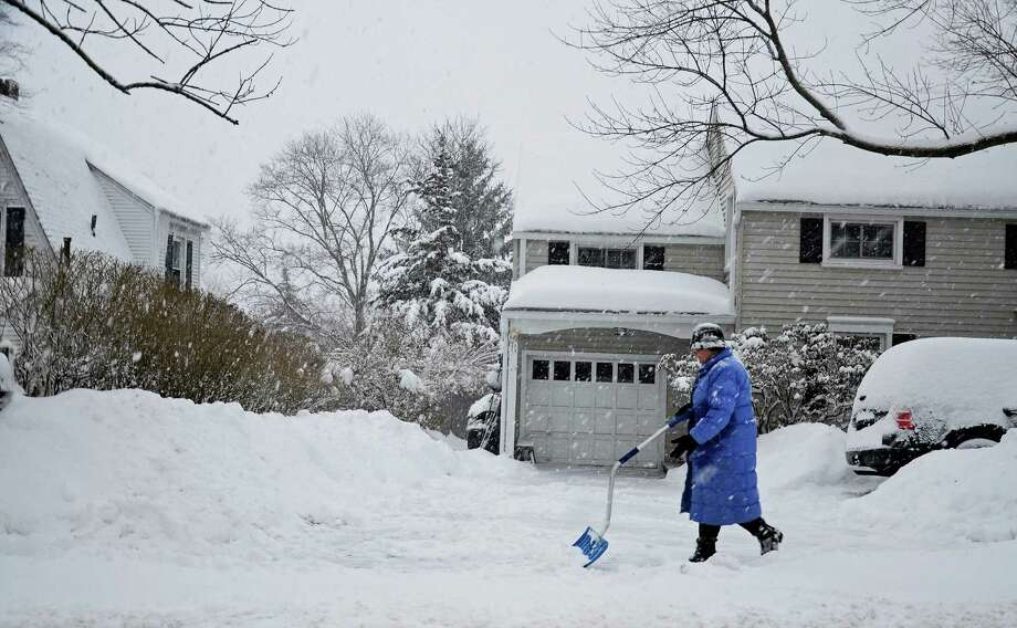 A Darien resident shovels the walkway outside her Hoyt Street home Thursday morning, Feb. 13. Photo: Nelson Oliveira / New Canaan News