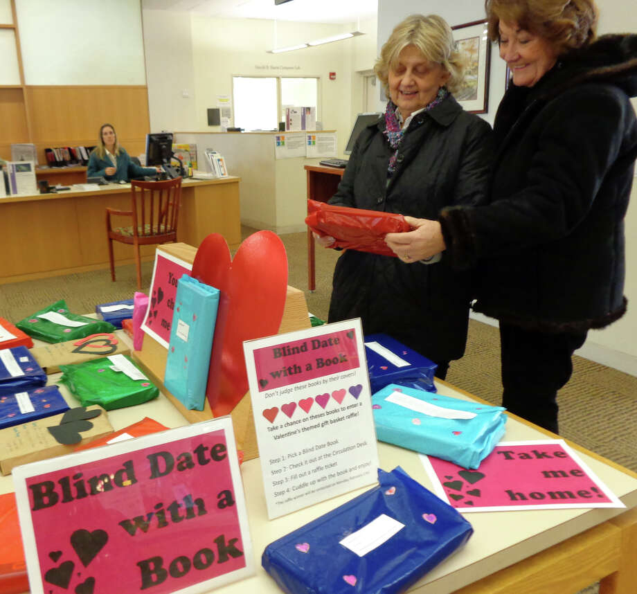 "Ginny Jacobs, left, and Rosemary Crossland, both of Fairfield, consider a blind date with a book at the Fairfield Public Librar, but decided they have too many other ""dates"" lined up with books waiting to be read at home. Photo: Meg Barone / Fairfield Citizen contributed"