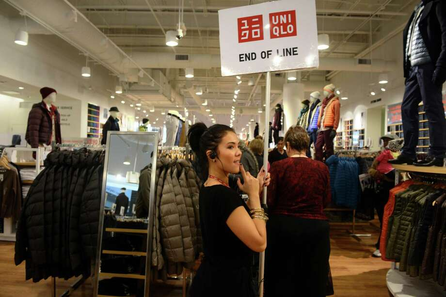 Ashley Bright, of Norwalk, holds up a sign at the end of a growing line of customers waiting to checkout at UNIQLO's new Westfield Trumbull Mall store Friday, Nov. 8, 2013 during their grand opening sale. Photo: Autumn Driscoll / Connecticut Post