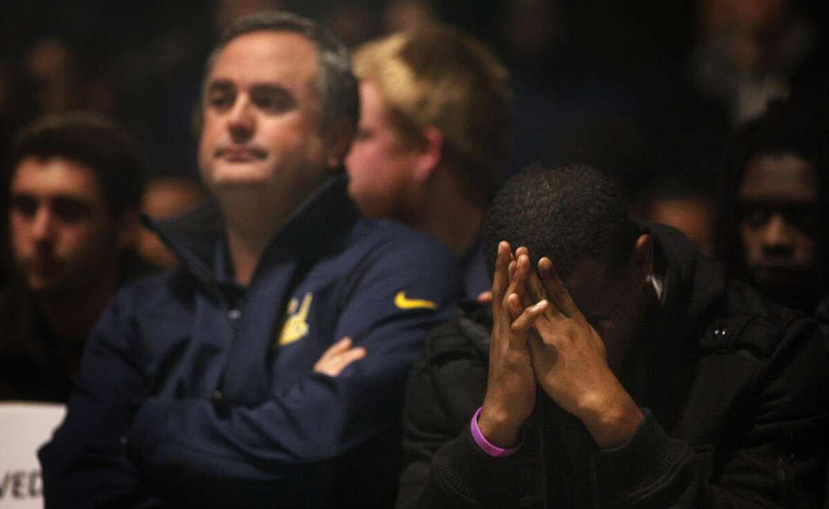 Cal Bears Football Coach Sonny Dykes , left sits with players as they gather to honor Ted Agu, Wednesday February 12, 2014, for a memorial service outside the Lisa and Douglas Goldman Plaza at the stadium at Cal Berkeley campus in Berkeley, Calif. Ted, 21-year old, passed away tragically last Friday morning following a team workout.