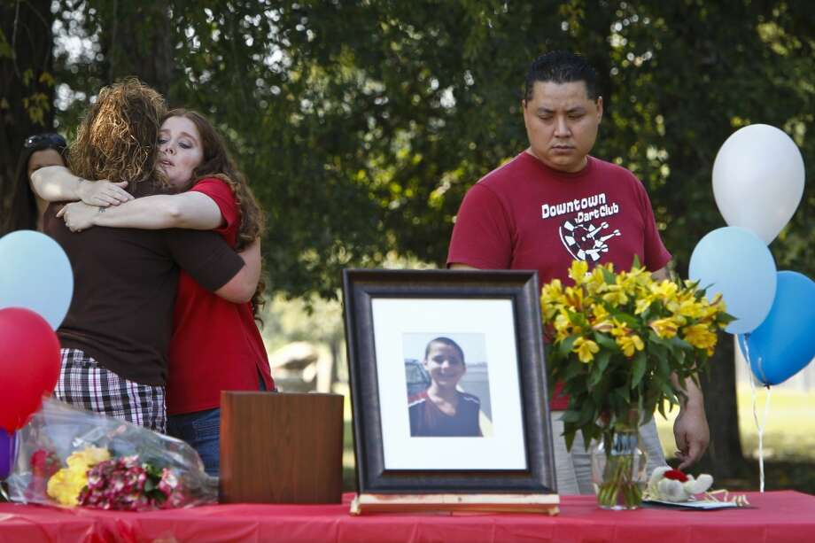 "Hannah Turpin, 13, (left), a classmate and friend of Asher Brown, gives Amy Truong, Asher's mother, a hug as her husband David Truong (right), reflects as he looks towards a photo of his stepson, Asher Brown, the thirteen-year-old boy who committed suicide as a result of school bullying last week, during a memorial service near Moore Elementary School Saturday, Oct. 2, 2010, in Houston.  Asher shot himself in the head with his stepfather's handgun on Sept. 23 at his family's home. Truong said his son, a straight-A student who loved to read, had been ridiculed by students at school because he was small, a Buddhist and didn't wear designer clothes.   ""What my child went through was not normal in any capacity,"" Truong said. ""It was relentless. It was just day after day and nothing was done and now my son is dead.""   ( Michael Paulsen / Houston Chronicle ) Photo: Houston Chronicle"