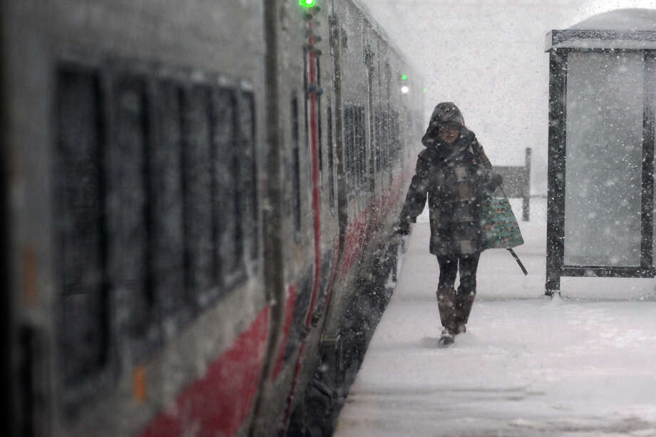 A rider disembarks a Metro-North train as heavy snow falls in Stratford, Conn. on Feb. 13, 2014. Photo: Ned Gerard / Connecticut Post