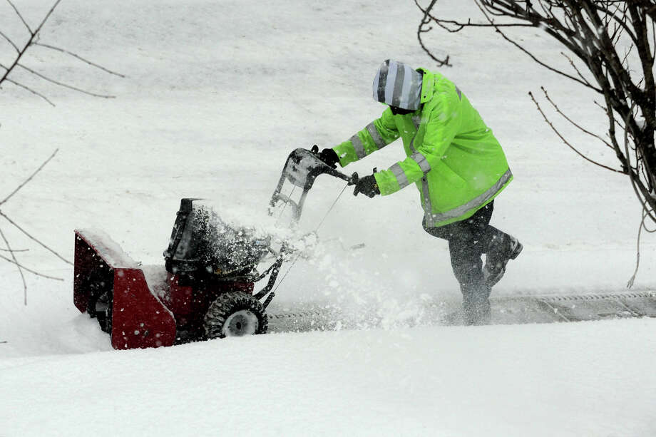 Brandon Blackwell runs a snow blower near the Stratford train station as heavy snow falls in Stratford, Conn. on Feb. 13, 2014. Photo: Ned Gerard / Connecticut Post