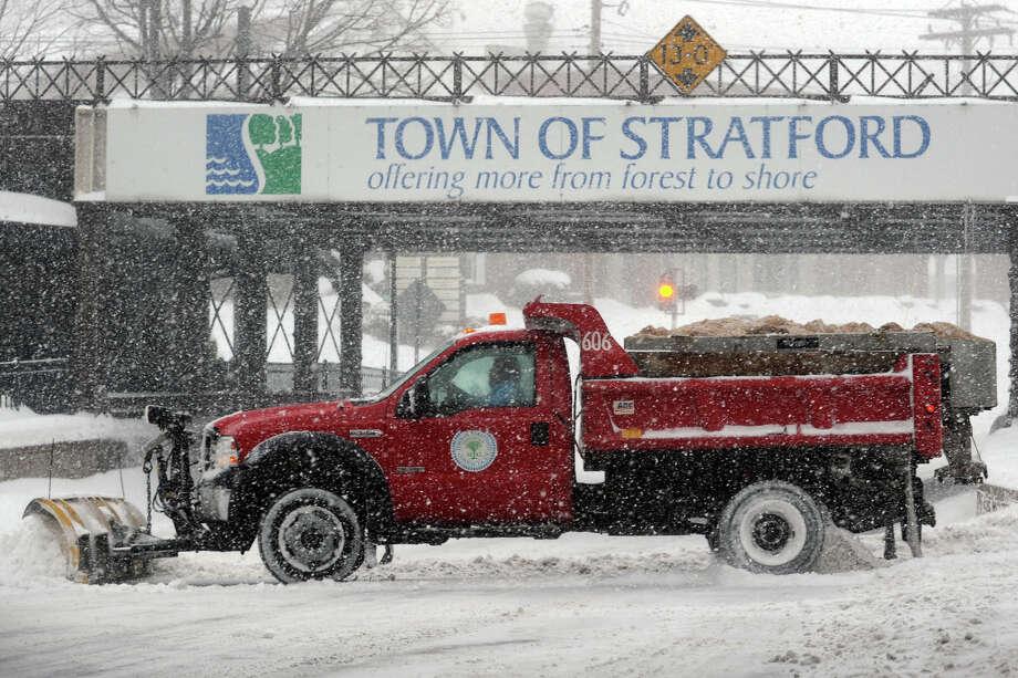 A town truck plows across Main Street as heavy snow falls in Stratford, Conn. on Feb. 13, 2014. Photo: Ned Gerard / Connecticut Post
