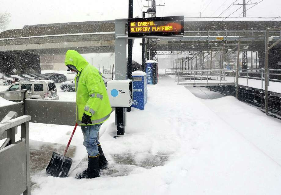 Town worker Victor Gabriel works to keep the platform clear at the downtown railroad station in Fairfield, Conn. on Thursday, Feb. 13, 2014. Photo: Cathy Zuraw / Connecticut Post