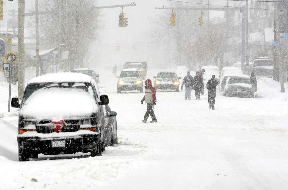 With many sidewalks still covered in snow from past storms, pedestrians take to the road on State St .in Bridgeport, Conn. on Thursday, Feb. 13, 2014. Photo: Cathy Zuraw / Connecticut Post