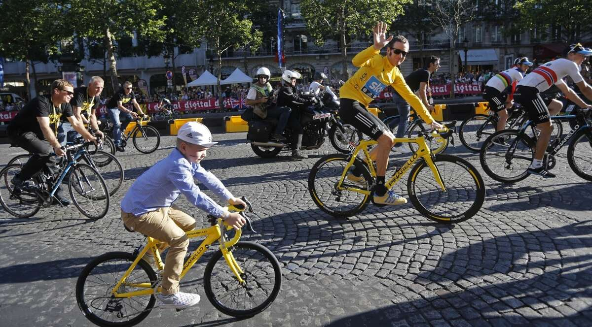FILE - In this Sunday July 22, 2012 file photo Bradley Wiggins, winner of the 2012 Tour de France cycling race, rides with his son during the team parade of the the Tour de France cycling race in Paris, France. Former Tour de France champion Bradley Wiggins says he had to find a new school for his children after they were