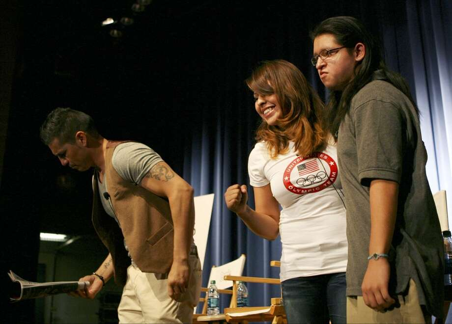 Olympian Marlen Esparza takes a photo with Alexander Herrera, a junior at Lanier High School, as Sergio Martinez signs autographs Aug. 30, 2013 after the two finished speaking to a packed auditorium of students at Sidney Lanier High School against bullying. The event, hosted by People en Espanol, allowed Martinez and Esparza to speak to the students about their experiences with bullying and what they had to overcome including strangers talking about them and social media. Photo: For The San Antonio Express-News