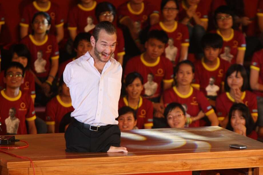 In this Thursday, May 23, 2013 photo, Nick Vujicic, a Serbian Australian evangelist who was born with no limbs, gives his speech to a crowd of about 25,000 students and young people at My Dinh national stadium in Hanoi, Vietnam. Vujicic, who is able to stand up and move around on his pelvis, shuffled round on a small table set up on a stage on corner of the field. In a talk laced with jokes, platitudes and attempts at Vietnamese, he spoke out against bullying and drinking; on the need for forgiveness and hope; and respect for family. All those themes resonate with Vietnamese and their leaders, one of whom - the vice president - was watching from the VIP area. (AP Photo/Na Son Nguyen) Photo: Associated Press