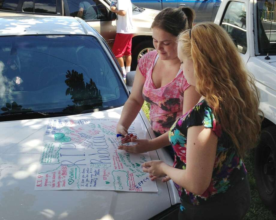 In this Sept. 10, 2013 photo, Summer Howard, 19 and Alecia Wilkins, 18, make a poster for Summer's sister Rebecca Sedwick. Polk County Sheriff Grady Judd said that Sedwick jumped to her death on Sept. 9, 2013, at an old cement business in Lakeland, Fla. Officials are looking into if they can file charges under a new Florida state law that covers cyber-bullying. (AP Photo/The Lakeland Ledger, Stephanie Allen) Photo: Associated Press