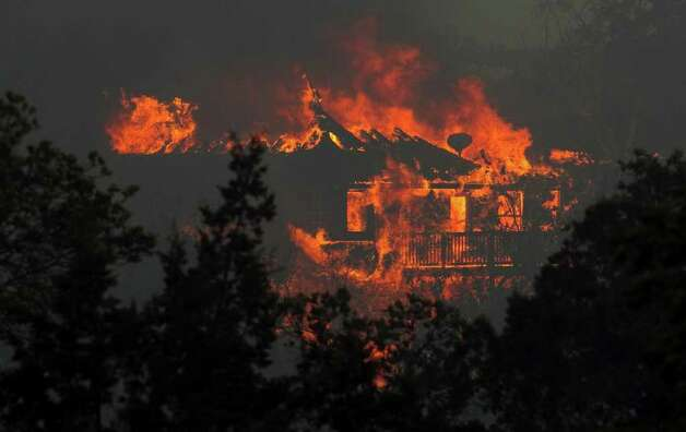 A fire burns a home in Steiner Ranch west of Austin, Texas, on Sunday afternoon, Sept. 4, 2011. The fires are forcing evacuations in Pflugerville, Steiner Ranch and Bastrop County. (AP Photo/Austin American-Statesman, Jay Janner) MAGS OUT; NO SALES; TV OUT; INTERNET OUT; AP MEMBERS ONLY Photo: Jay Janner, MBR / Austin American-Statesman